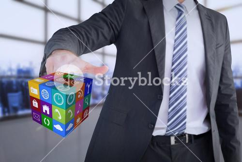 Composite image of businessman pointing at cube with his finger