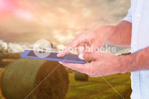 Composite image of a man using tablet computer against field landscape