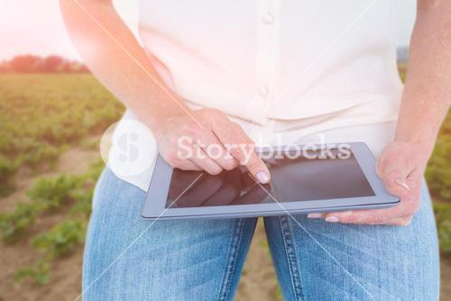 Composite image of woman using tablet pc against rural landscape