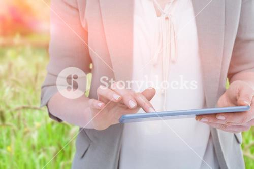 Composite image of close up of woman using tablet against green landscape