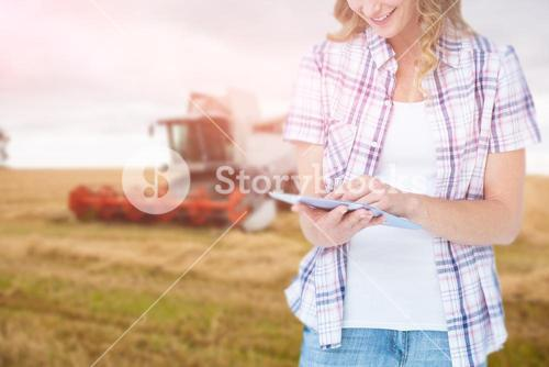 Composite image of pretty hipster using tablet against agricultural scene