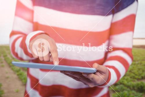 Composite image of mid section of woman using tablet against green landscape