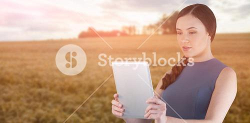 Composite image of beautiful woman using digital tablet