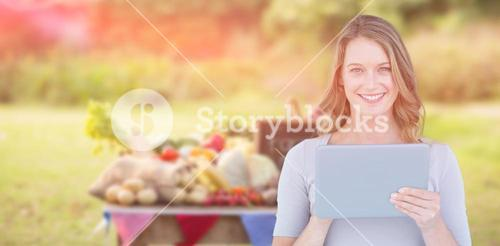 Composite image of portrait of happy woman holding digital tablet