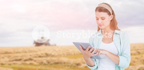 Composite image of pretty hipster using tablet