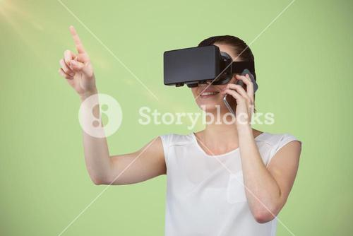 Composite image of beautiful woman gesturing while suing virtual reality headset and talking mobile