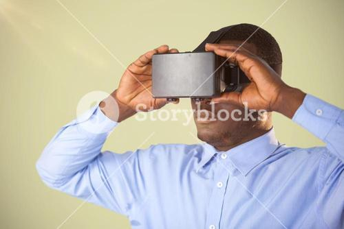 Composite image of man holding virtual reality headset