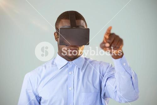 Composite image of man standing while wearing virtual reality headset