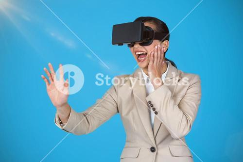 Composite image of excited businesswoman wearing virtual video glasses