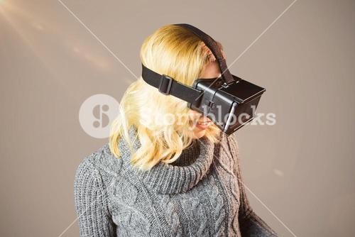 Composite image of blond woman using virtual reality headset
