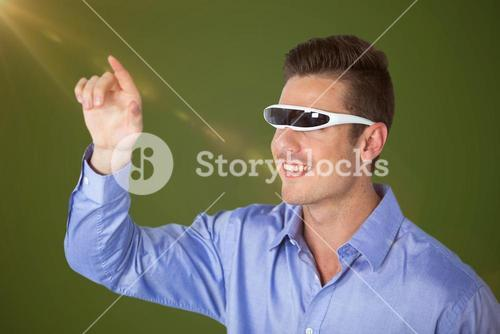 Composite image of smiling man pointing while using virtual video glasses