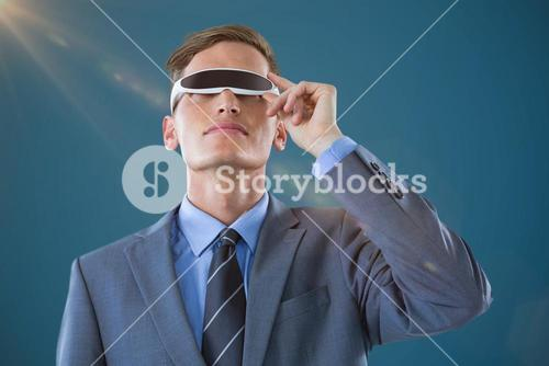 Composite image of businessman using virtual reality glasses against blue background