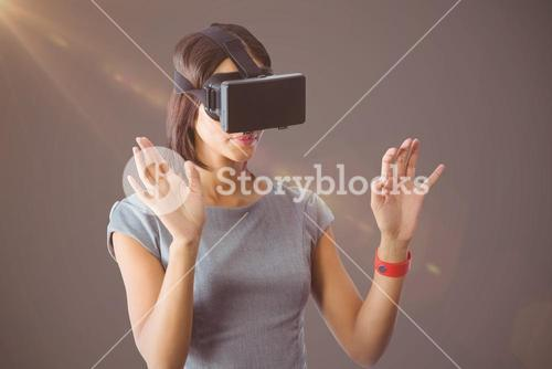 Composite image of businesswoman holding virtual glasses on a grey background