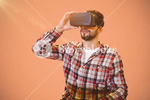 Composite image of casual man man holding virtual glasses on a pink background