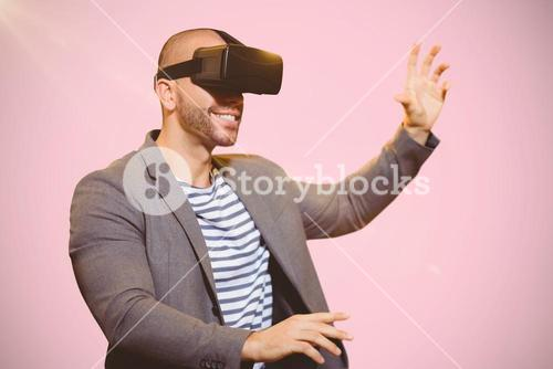 Composite image of businessman holding virtual glasses on a pink background