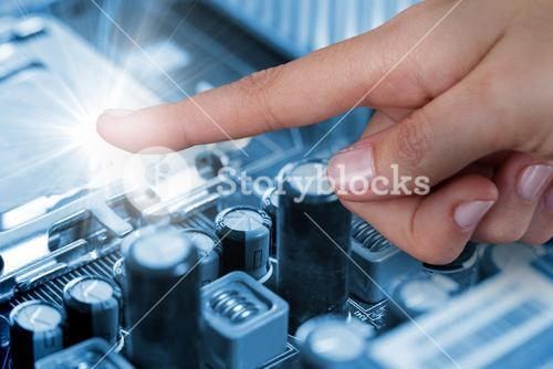 Composite image of human hand pointing at parts in circuit board