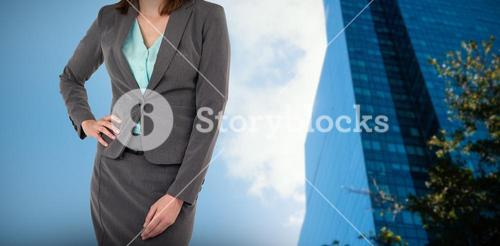 Composite image of midsection of businesswoman with hands on hip