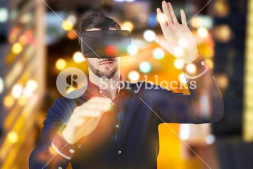 Composite image of businessman holding virtual glasses on a light background