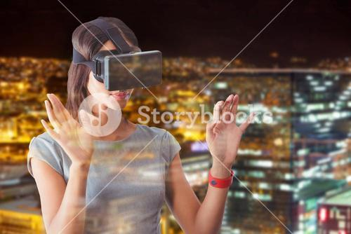 Composite image of businesswoman holding virtual glasses on a light city background