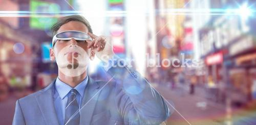 Composite image of businessman using virtual reality glasses against blurry background