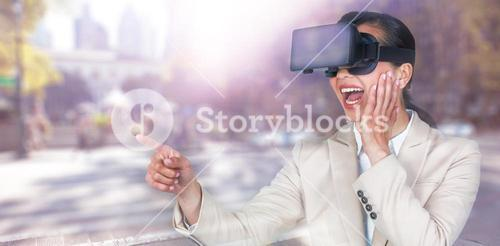 Composite image of excited businesswoman pointing while wearing virtual video glasses