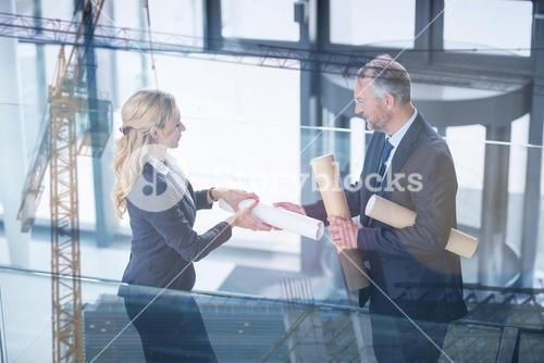 Composite image of building construction site against business colleagues discussing