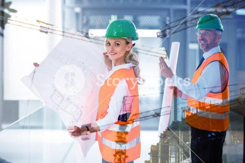 Composite image of collegues holding plans on building construction site
