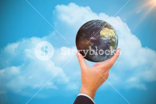 Composite image of businessman presenting earth with his finger