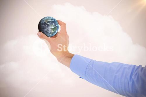 Composite image of businessman holding little earth in presentation