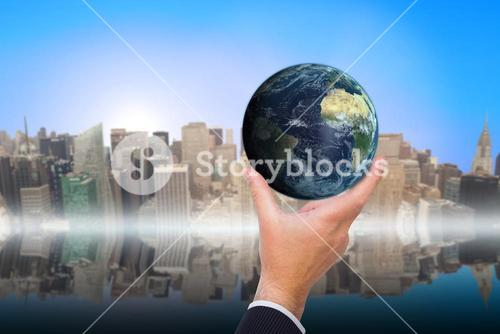 Composite image of businessman pointing little earth with his finger