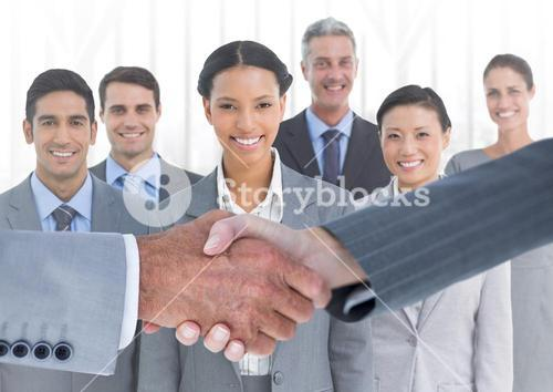 Handshake in front of business people in office against white background