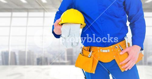 Carpenter with gloves against window background