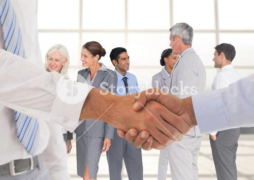 Handshake in front of business people at window