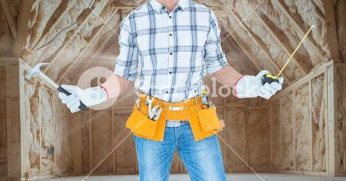 Carpenter with hammer and measuring tape in attic with flare