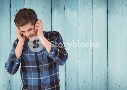 Man with headphones against wood panel