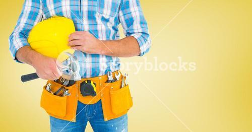 Carpenter with hammer against yellow background