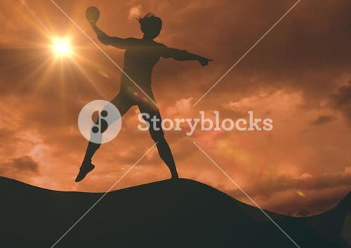 Silhouette making volleyball against sky with flare