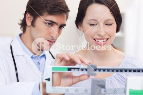 Doctor and patient adjusting the scale