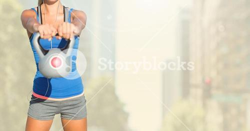 Fitness woman torso listening music and making fitness exercises against city background