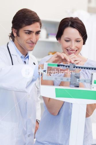 Male doctor adjusting scale for his patient