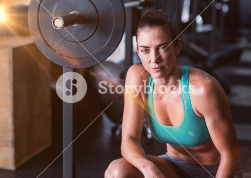 Fitness Woman and weights with flare in a gym