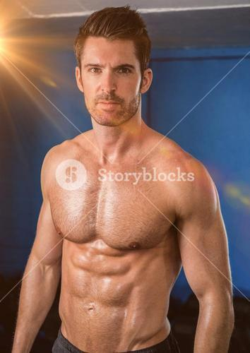 Body builder with flare against a blue wall