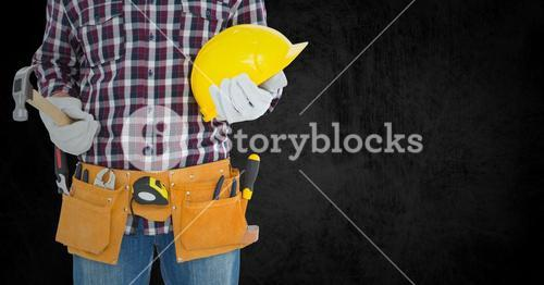Carpenter with hammer against black background