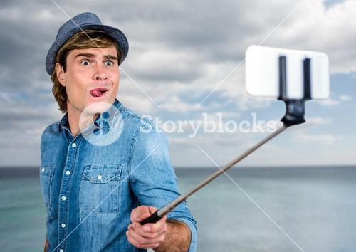 Man with selfie stick in front of sea
