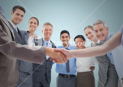 Handshake in front of business people with blue background