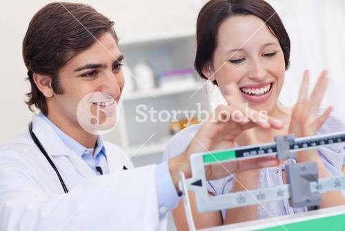 Male doctor adjusting scale for excited patient