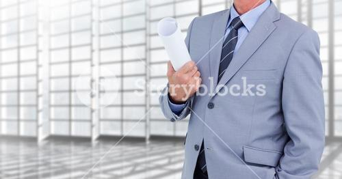 Architect Torso holding plans in a corridor against windows