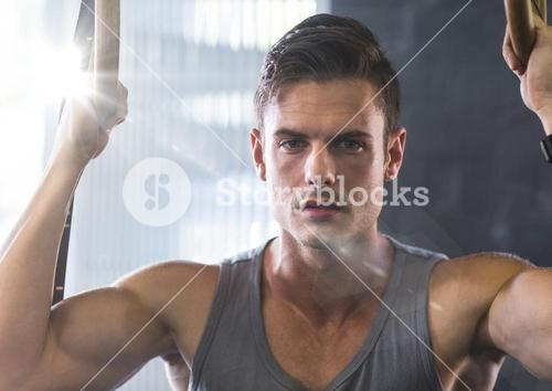 Composite image of Man doing pull ups with flare