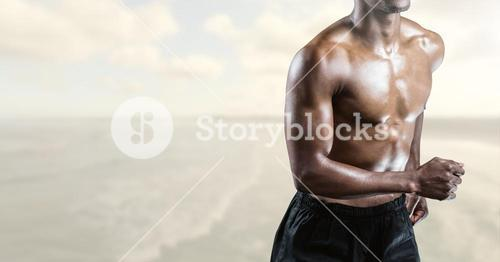 Composite image of man Fitness Torso against sea in background
