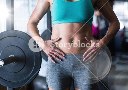 Composite image of Woman's torso in gym with flare